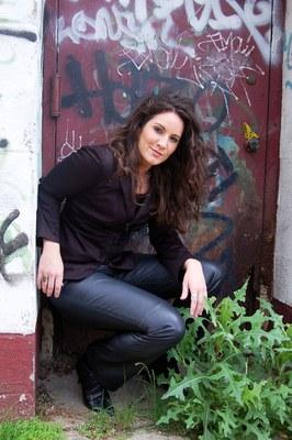 Emily in leather pants infront of metal door